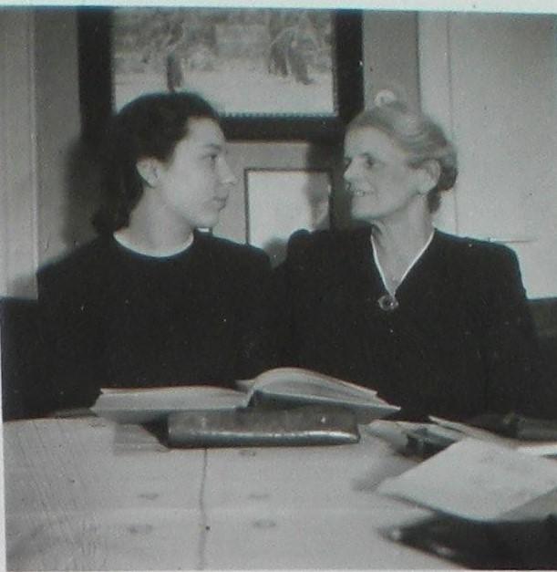 Hanni Watzinger, die Ehefrau von Helmut Watzinger, sitzt mit ihrer Schwiegermutter Marie am Esstisch. Marie ist auf Weihnachtsurlaub aus Göppingen zu Hause. Maries Gesicht wirkt eingefallen. Vor den beiden Frauen liegt ein Buch.