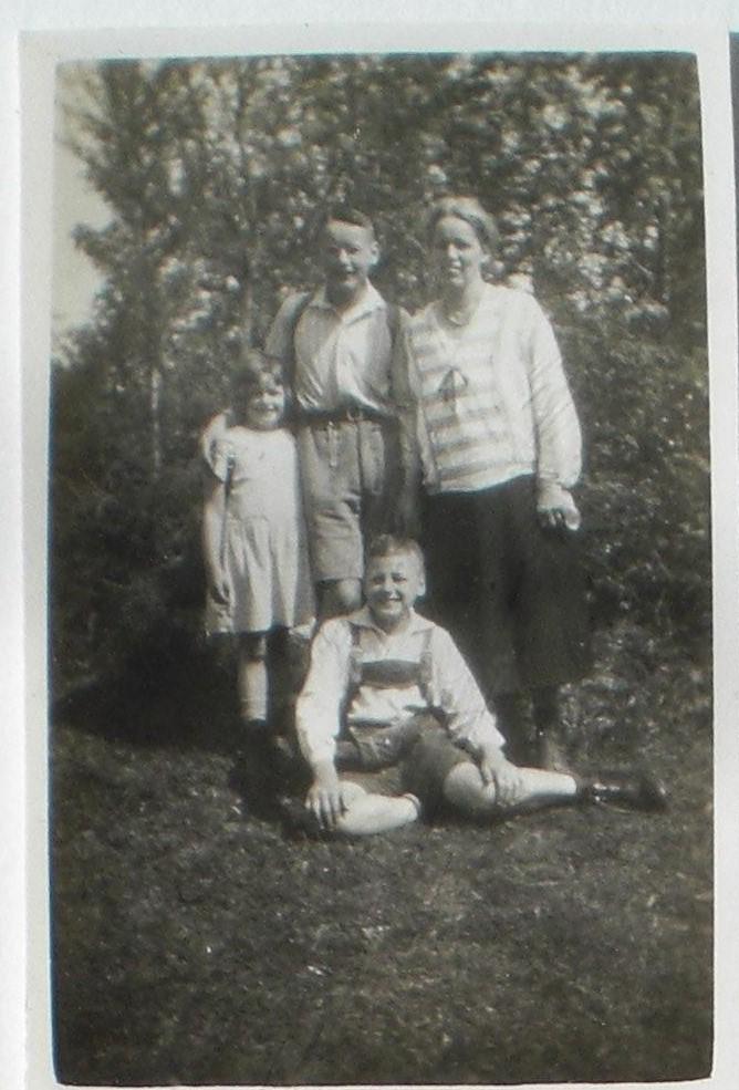 Marie mit ihren drei Kindern Karl Otto, Irmgard und Helmut auf einer Wiese. Marie und Irmgard umrahmen Karl Otto. Helmut sitzt in Lederhosen auf dem Gras. Die Beine nach hinten zur Seite geschwungen.