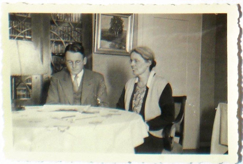 Karl Otto Watzinger und seine Mutter Marie sitzen am Esstisch. Karl Otto blickt nach unten.Marie lächelt. Im Hintergrund ist eine Vitrine mit Büchern zu sehen. Es ist eine schwarz-weiß Aufnahme.