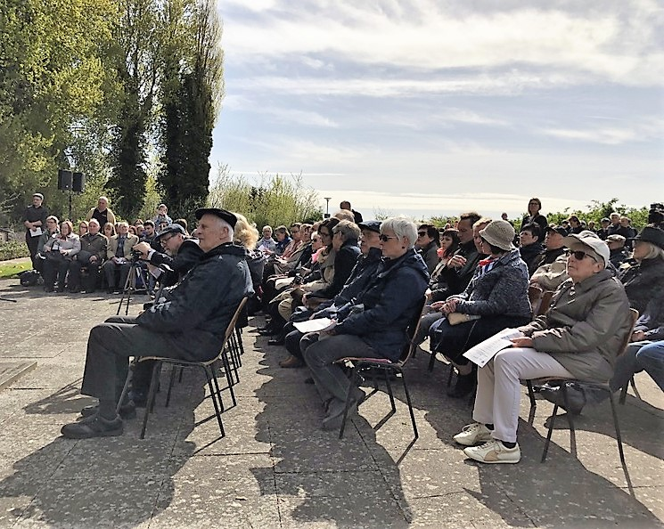Three rows of guests and general public seated at the commemorative service in Neustadt. There are more rows in the background of the picture. Few people are standing.