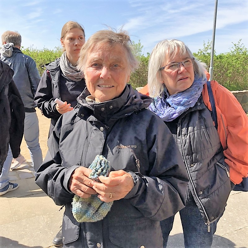 In the center of the picture you see Kaethe Birkenfeldt who, at age 12, saw Nazis dump ammunition from the evacuating train of Muna Lübberstedt into Lake Dieksee, Timmdorf. She is holding a woolen hat in her hands. She looks much younger than 86. In the background you see two women looking to something going on left of the photographer.
