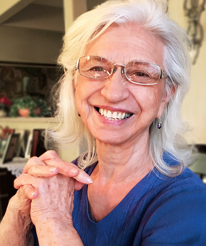 Portrait of Lilia Meneguzzi taken in 2017 showing a smiling woman with white hair.