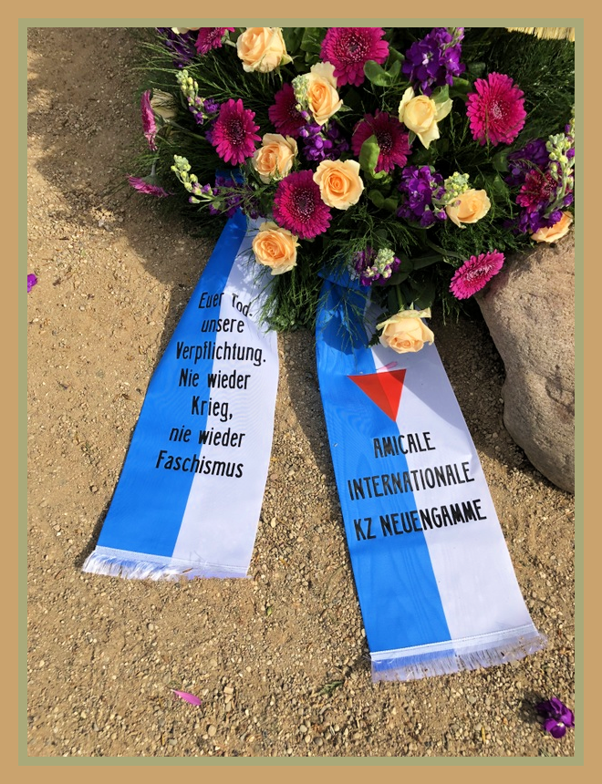 wreath by the Amicale Internationale KZ Neuengamme with yellow and dark pink flowers and a blue and white ribbon.