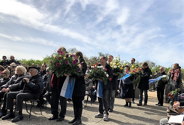 People holding wreaths waiting to be allowed to step close to the commemorativve stone in Neustadt.