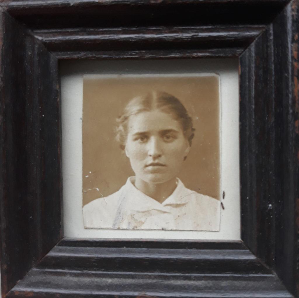 Portrait von Großmutter Nina. Sie trägt eine weiße, hochgeknöpfte Bluse. Die Haare in der Mitte gescheitelt und im Nacken zusammengesteckt.