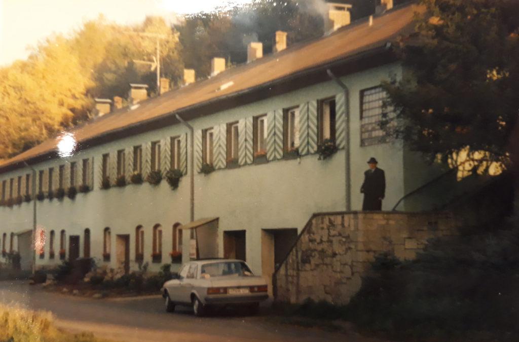 Reihenhäuser in weiß. Ein Auto parkt vor einer Treppe. Auf dem Treppenabsatz steht Jan G. mit Hut.