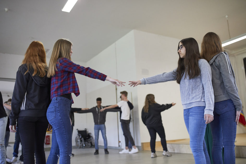 Students of a high school from Hamburg are performing a play. They are standing in circles, touching each other outstretched finger tips.