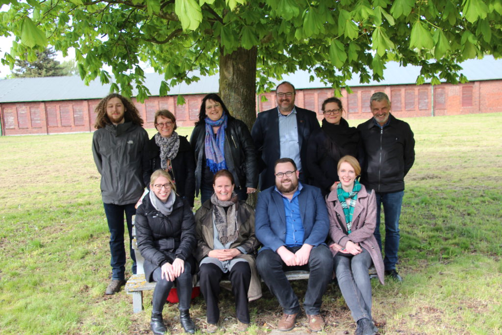 Picture of founding members of the Young Committee. Half of the group are standing below a Maple tree. The others are seated on a bench in front of them. Behind them you can see the red bricks of the former Walther factory that is now part of the Neuengamme Concentration Camp Memorial.