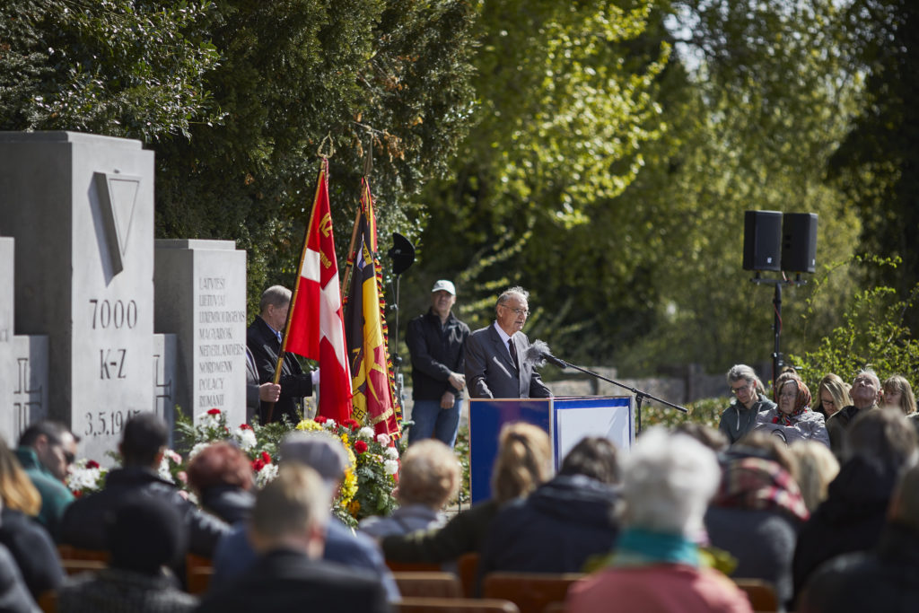 Jean-Michel Gaussot, president of the Amicale Internationale KZ Neuengamme, standing in front of the commemorative stone in Neustadt giving a speech to remember the prisoners who had died in the Bay of Lübeck 73 years earlier.