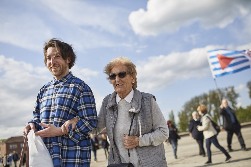 Mindu Hornick (right) holding on to her grandson's arm. Both are smiling. Above them the blue sky.