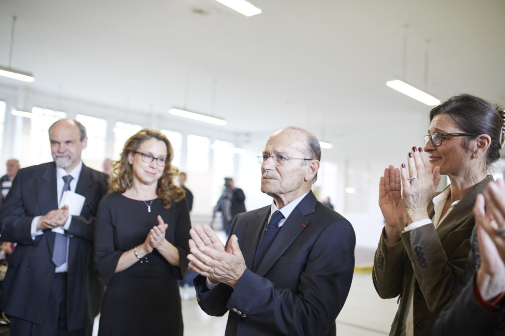 Survivor Pascal Vallicioni is applauding somebody (possibly students who just finished a performance) after the commemorative service held at the Neuengamme Memorial on May 3, 2018. To his right are Carola Veit (President of Hamburg Parliament) and Dr. Detlef Garbe, Director of the Memorial). On his right is his daughter Pascale Evans clapping while her face is wrinkled with emotions.