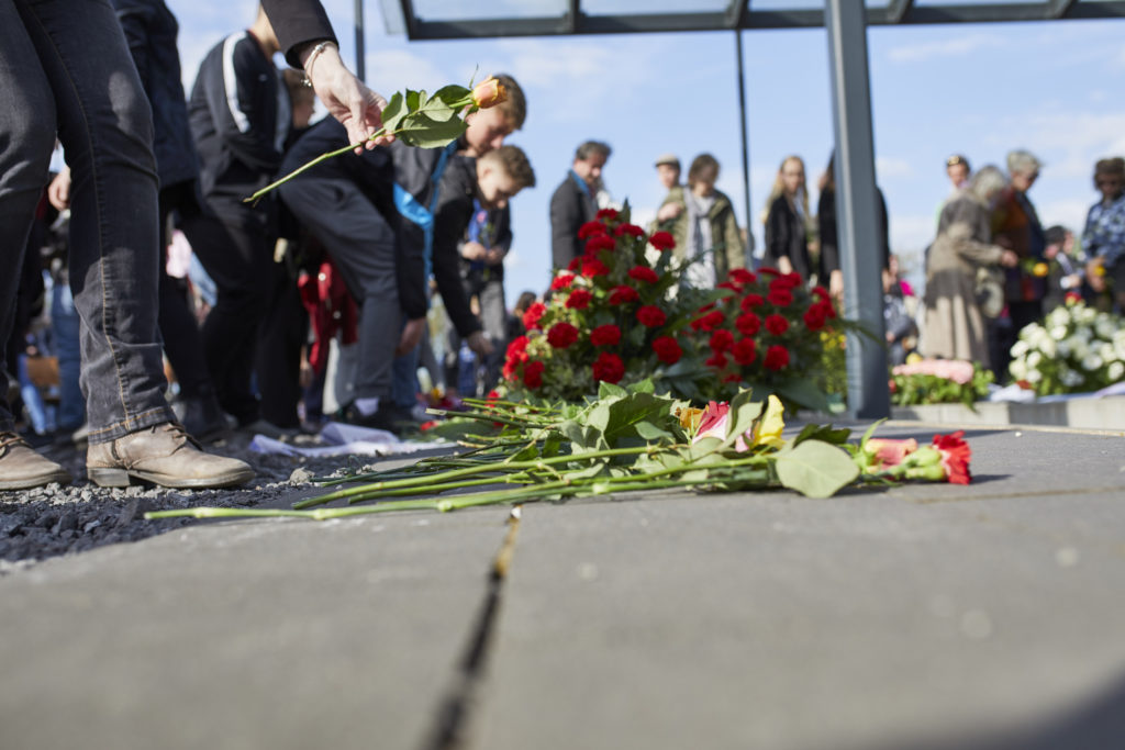 In the foreground flowers and wreath as well as feet and legs of young people laying them down at the site of the former detention bunker on May 3, 2018. In the background one can see people still putting down flowers.
