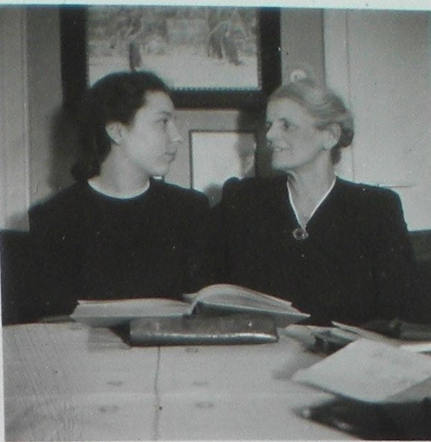Marie (right) and her daughter in law Hanni sitting at a table with some books in front of them. Hanni is looking at Marie, but Marie seems to gaze past her. Both women are dressed in black with little white collars.