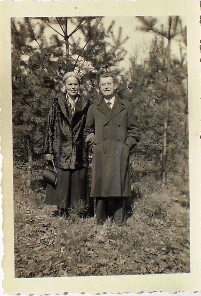 Marie and her husband Carl standing on a slope them wearing fancy winter coats. Behind them seveal needle trees can be seen.