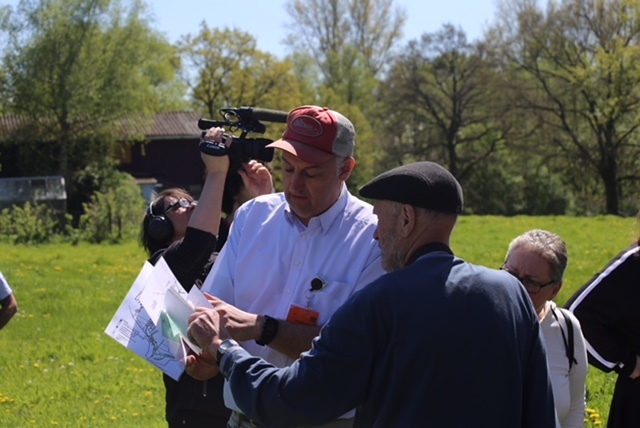 Hartmut Oberstech in a white shirt and basebal cap and Erdwig Kramer in a dark shirt are looking at a map of the grounds of the former concentration camp. Behind them there is the camera man filming the outing.