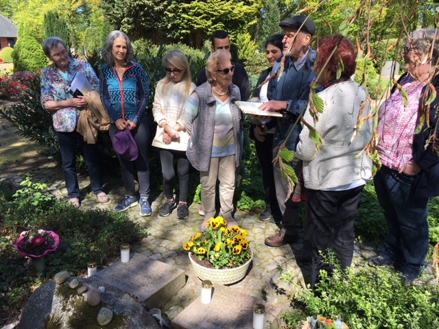 Erdwig Kramer is praying while holding a book at the communal grave for the slave laborers who were killed. He is surrounded by volunteers from the Muna association as well as survivors Barbara Lorber and Mindu Hornick and their families.
