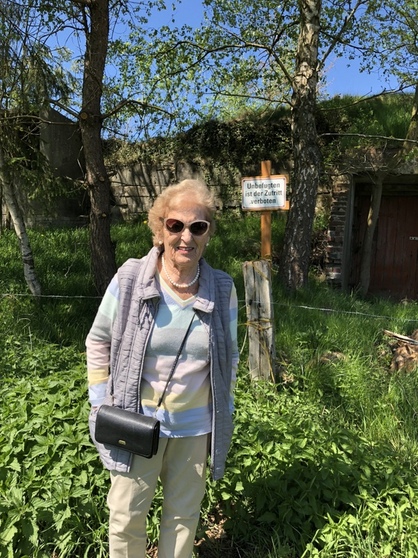 Mindu Hornick standing in front of the air raid shelter she hated to enter as a prisoner. She is smiling at the camera, wearing dark sunglasses.
