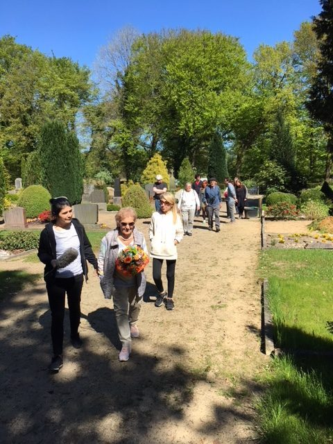 Mindu Hornick is carrying flowers to the communal grave of the dead prisoners. Her minder walking next to her is carrying a microphone for the camera team recording this visit. Behind them is Nicola Foster, Mindu's daughter. The rest of the group is in the very back.