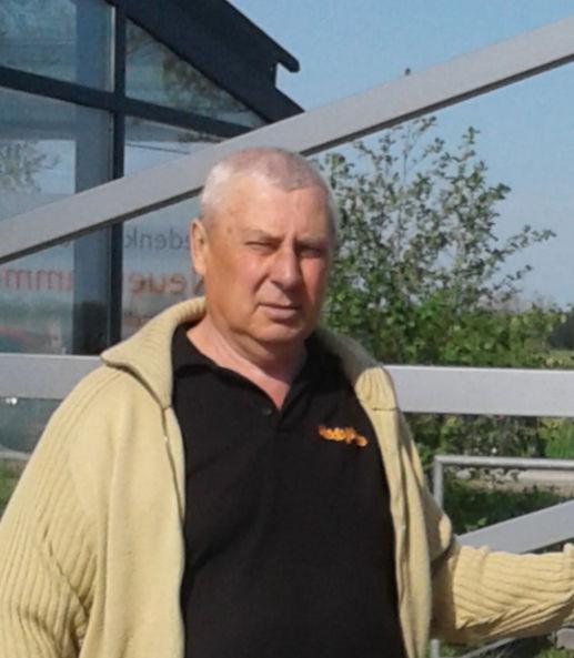 Mykola Titow vor dem stilisierten Lagertor am Haupteingang zur KZ-Gedenkstätte Neuengamme.