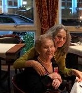 Roslyn Eldar (in green sweater) and Mindu Hornick smiling at the camera while sitting in a restaurant in Hamburg celebrating Mindu's birthday.
