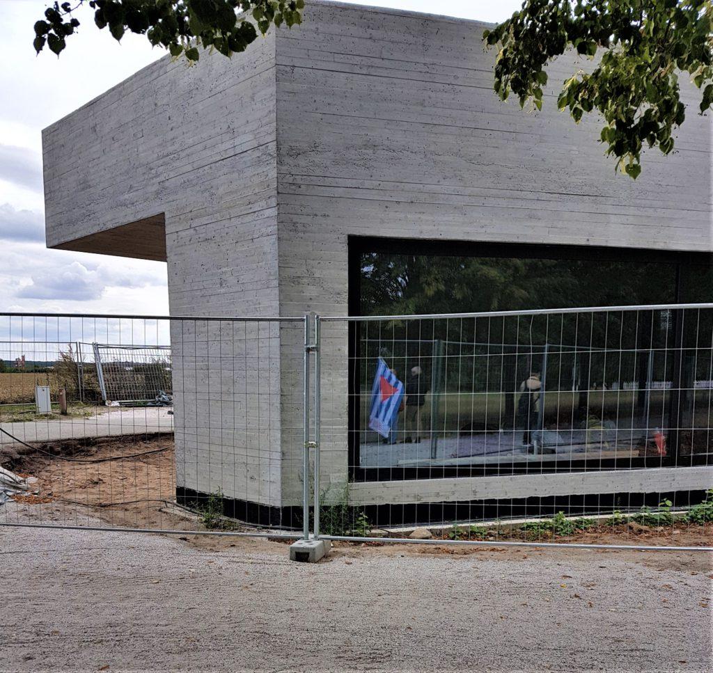 Hinter dem Bauzaun steht der graue, eckige Flachbau des zukünftigen Dokumentationszentrums. In der Fensterscheibe spiegeln sich Teilnehmer_innen des Besuchs.