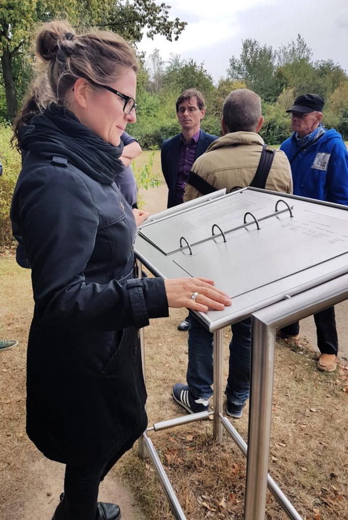 Christine Eckel, Generalsekretärin der AIN, liest im Gedenkbuch. Hinter ihr steht Herr Froese (Mitte) und spricht mit einigen Teilnehmern.