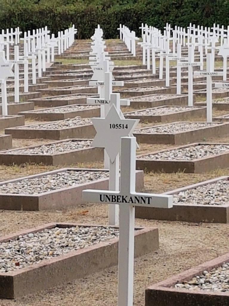 """Gräber auf dem Ehrendfriedhof. Die Grabstätten sind mit Kieselsteinen bedeckt und umrandet von rotem Klinker. Weiße Kreuze oder weiße Davidssterne ragen empor. Auf dem vordersten Kreuz steht """"Unbekannt."""" Dahinter folgt ein Davidsstern mit einer Nummer."""