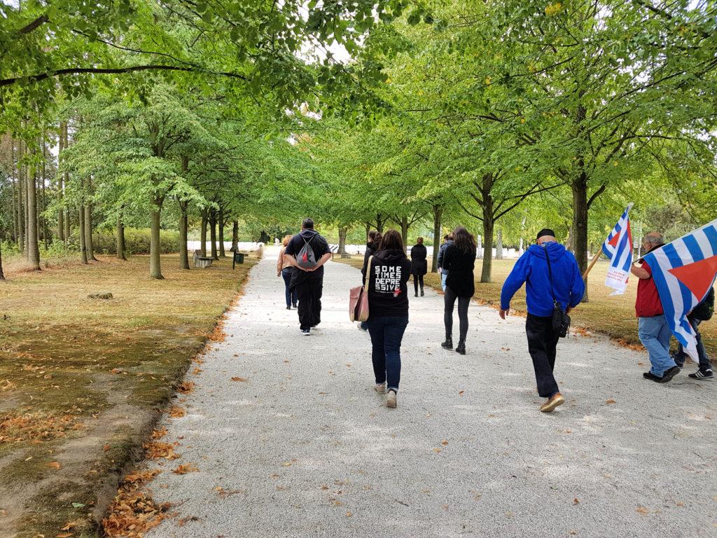 Der Weg zum Ehrendfriedhof ist gesäumt von Bäumen, die noch grüne Blätter tragen. Die Teilnehmer ziehen mit gesenkten Köpfen zu den Gräbern. Mitglieder der VVN Prignitz tragen Fahnen.