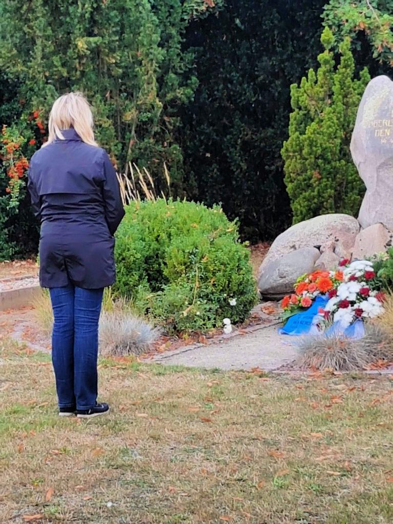 Uta Kühl, Vorsitzende der AGN, hat so eben einen Kranz am Gedenkstein niedergelegt. Mit dem Rücken zur Kamera hält sie einen Moment am Gedenkstein inne.