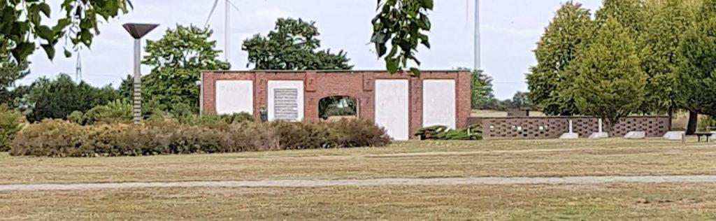 In einiger Entfernung steht die rekonstruierte Mauer der Feldscheune. Wo Türen waren sind nun weiße Wände. Auf einer ist ein Schriftzug. Links neben der Mauer ist eine kleine Mauer, die den Gedenkhain säumt.